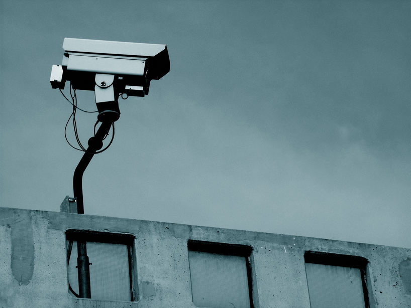 image of a surveillance camera on an urban rooftop